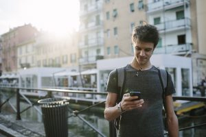 Young-Caucasian-Male-texting-near-canal-300x200
